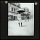 [Man wearing uniform carrying umbrella in street]